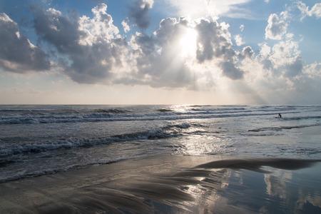 mare agitato: raggi del sole filtrare attraverso le nubi sul mare agitato e la spiaggia, mentre un ragazzo va surf
