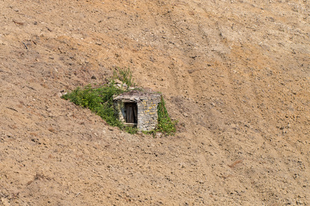 unused: Old well made of stone almost covered by spontaneous vegetation  in a steep ploughed field Piedmont Italy Stock Photo