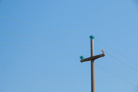 cement pole: Power Pole made of cement concrete  supporting a overhead power line with glass insulators blue sky in background