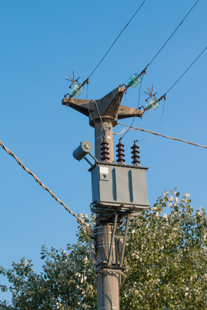 cement pole: Electric Transformer on a cement concrete power pole blue sky in background Stock Photo