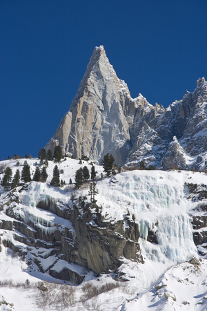 aiguille: Aiguille du Dru mountain of the Mont Blanc Massif in the French Alps, blue sky in background