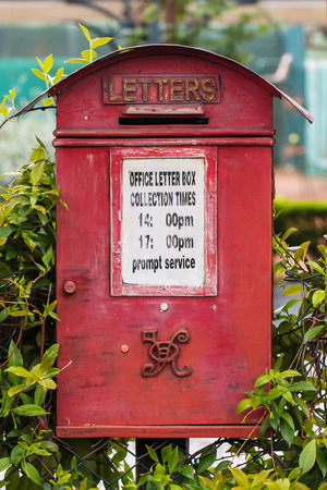 royal mail: Old Royal Mail letter box painted in red with monogram Queen Victoria and collection time indication