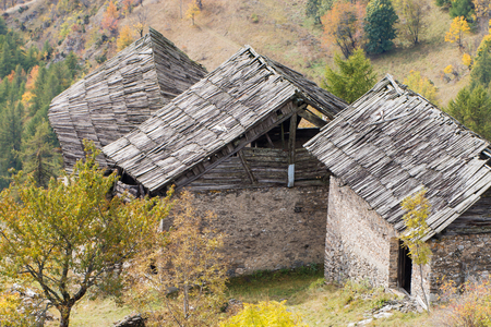 chalets: Old damaged wooden roofs made of larchs planks  covering three abandoned chalets in Italian Alps
