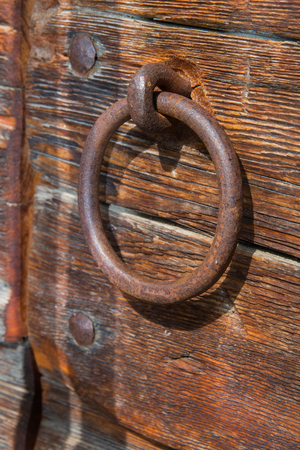 medieval blacksmith: Old rusty door handle ring shaped on a wooden door Stock Photo