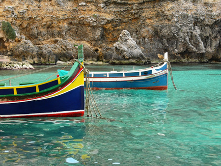 crystal clear: Colorful eyed fishermans boat called Iuzzu tipical of Malta anchored in a crystal clear water