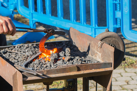 horse shoe: red hot horse shoe in a portable coal furnace taken to forge with pincers Stock Photo