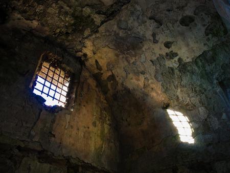 prison cell: prison de prison en ruine d'un château médiéval. la lumière du soleil entre par une fenêtre avec ironie rouillé barres Banque d'images
