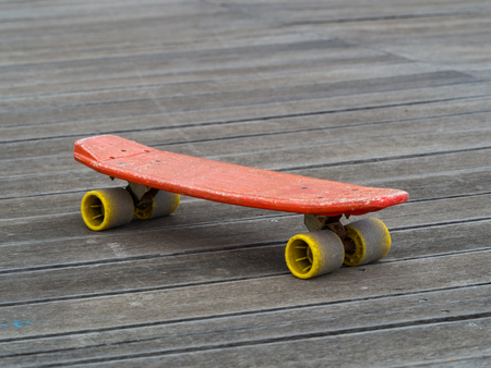 skate board: old skate board made of red and yellow plastic on wooden surface