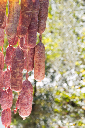 air dried salami: group of fresh hand made salami sausages displayed for sale in a country fair