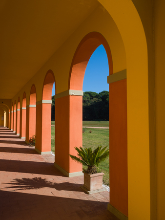 roofed house: perspective view of an arched walkway  in a sunny day