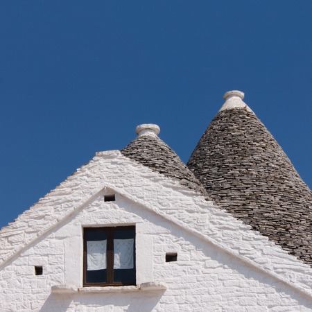 dry stone: Trulli of Alberobello Apulia italy detail of typical conical roofs made of dry stone. Blue sky in background Stock Photo