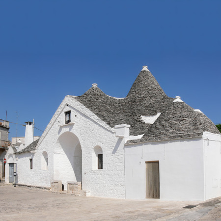 calcareous: Trullo sovrano biggest famous traditional building of Alberobello Bari Apulia Italy in a sunny day. Made of dry calcareous stone with typical cone roofs