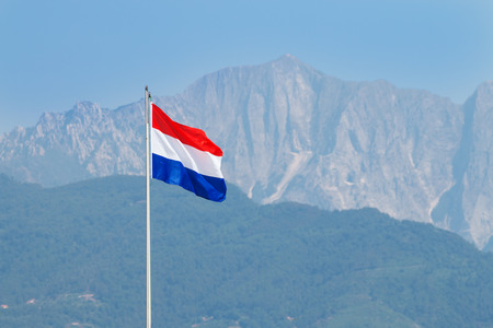 forte: flag of the Netherlands waves in the wind on a tall pole in Forte dei Marmi. Monte Altissimo of Allpi Apuane blurred in background Stock Photo