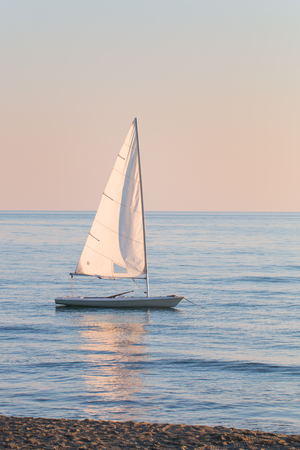 anchoring: small sailboat in the water anchored next to the beach in a summer sunset ready to sailing with the last breeze of the day. vertical