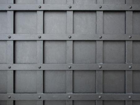 iron cross: Geometric pattern of squares grid on a gray iron door