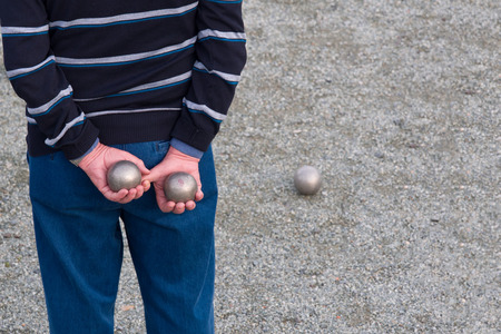petanque: Man holding two metal balls behind his back playing petanque
