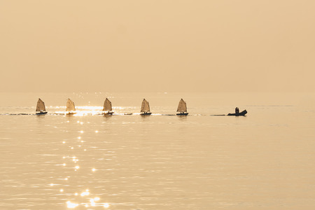 towed: Line of Optimist  (Small learning sails)  towed into port bu rubber boat in sephia golden atmosphere of sunset