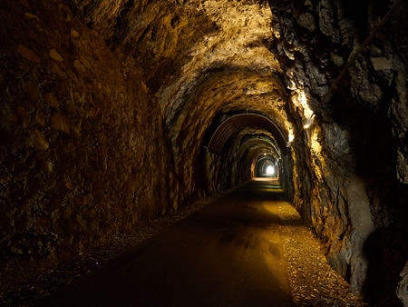 appears: Old Dark Tunnel Carved in Stone. Day Light appears at the end Stock Photo