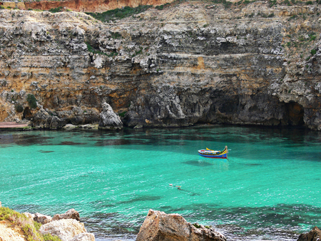 crystal clear: Colorful eyed fishermans boat called Iuzzu tipical of Malta anchored in a crystal clear water bay in Gozo