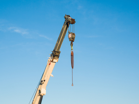 telescopic: Detail of a telescopic boom of a truck mounted crane with chains hanging on the hook, blue sky in background Stock Photo