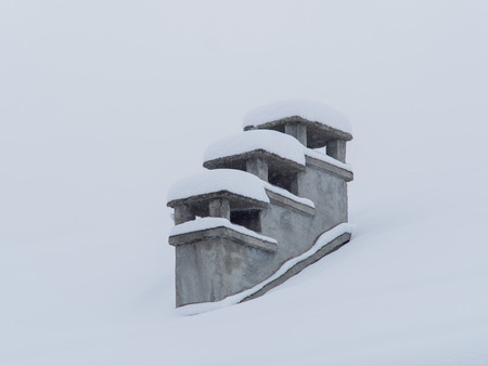 old gas stove: three old concrete chimneys covered by blanket of snow in winter During a snowfall Stock Photo