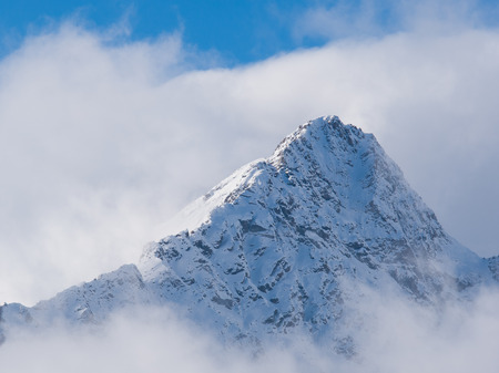 pyramid peak: Mountain peak full of snow surronded by clouds in the Alps Stock Photo
