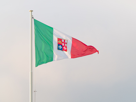 flit: tricolour triangular flag of Italian republic with naval jack in the middle fluttering in the wind Stock Photo