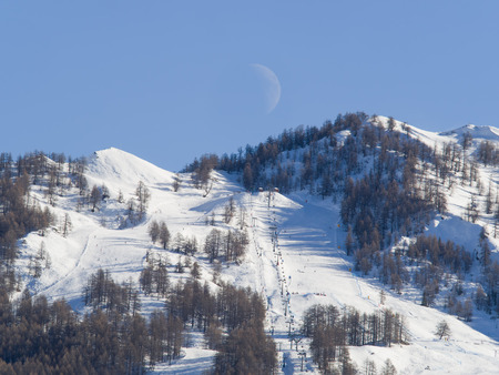 mountain landscape with ski slopes, ski lifts, woods, peaks,  and half moon in the blue sky Stock Photo