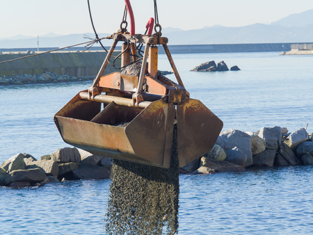 Dredge Clamshell Bucket unloading gravel in the water of a port next to the shore to replenish a beach