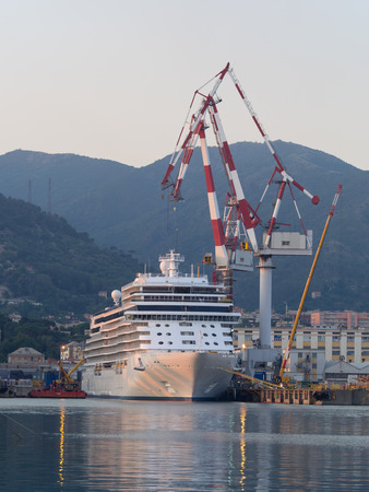 shipbuilding: Genoa, Italy _ july 01, 2016: Cruise ship moored at a dock of a shipyard with large cranes