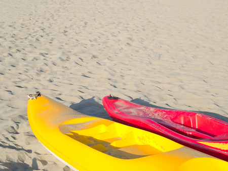 colorful (yellow and red) canoes on a light sandy beach. Detail of bows