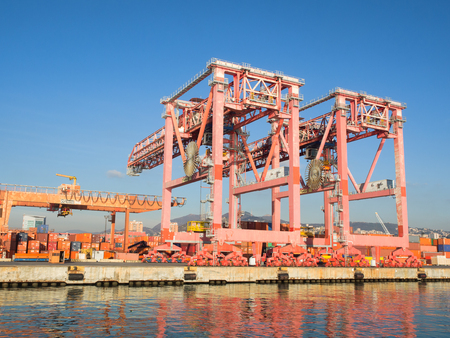 Genoa , Italy _ December  23, 2017: big red cranes used in ports to load and unload containers from cargo ships