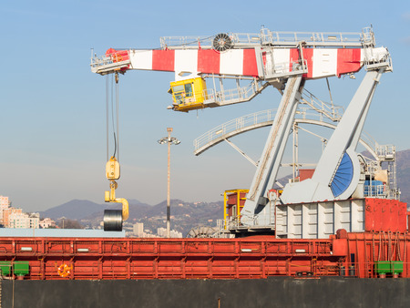 Genoa Italy_December 23, 2017: big port crane loading rolled steel sheet coil in a cargo ship