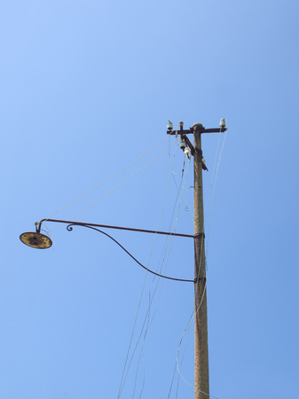 Old abandoned street light, wit broken wires, blue sky in background Stock Photo