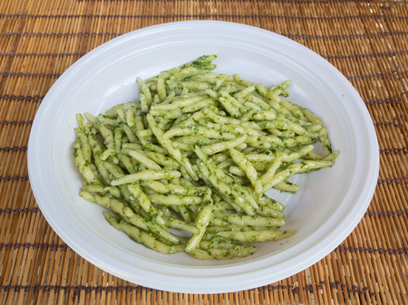 dish of trofie al pesto on a straw place mat : traditional handmade pasta with basil sauce made in Genoa (Liguria Italy)