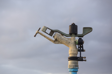 Impact irrigation Sprinkler used to irrigate agricultural crops, fields, lawn, golf course. cloudy sky in background