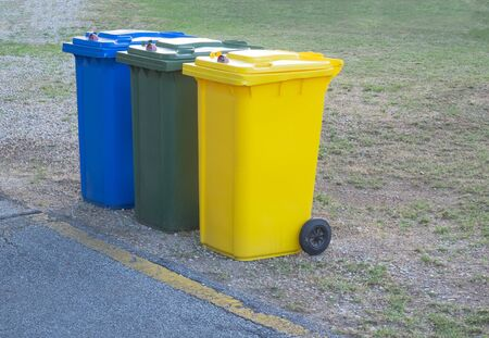 three lockable  recycle trash bins (blue, green, yellow) used for different materials   스톡 콘텐츠