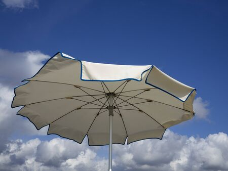 white beach umbrella viewed from above sways by the sea breeze. Blue sky with white clouds background, copy space 스톡 콘텐츠