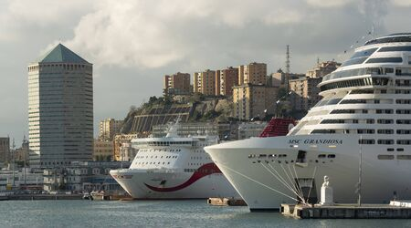 Genoa Italy_December 7, 2019: port with big cruise ship and ferry, matitone tower and city skyline in background