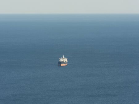 empty oil tanker alone in the middle of blue calm ocean