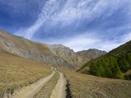 dirt road leads to the peaks of the mountains in a fall sunny day Archivio Fotografico