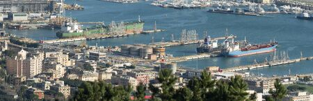 Genoa Italy_March 14, 2020:  Oil port next to the buildings of the city, with large tanks and three chemical tankers moored