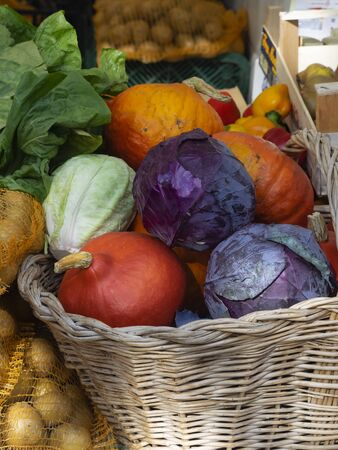 wicker basket full of colorful pumpkins and cabbage for sale with other vegetables in a country market Archivio Fotografico