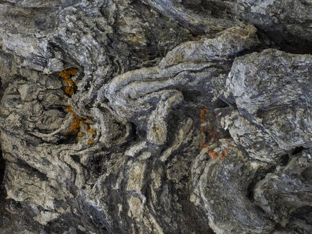detail of  wrinkled and striated rock with  reddish lichen on