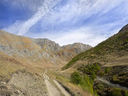 dirt road leads to the peaks of the mountains in an alpine valley
