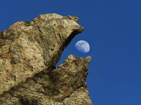 strange beak-shaped rock eats the almost full moon. Blue sky in background