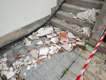 rubble (cement plaster and brick) fallen from a building after a weak earthquake ,  red and white signaling tape delimits the area