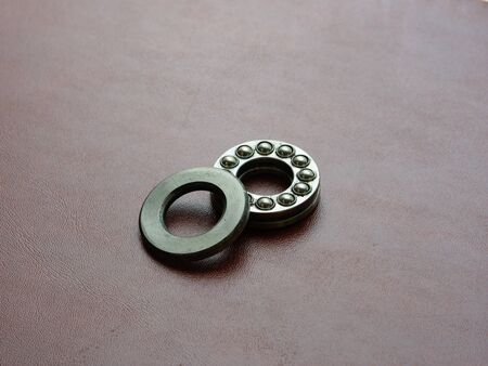 Thrust ball bearing open, used to accomodate axial loads, brown leather background Archivio Fotografico