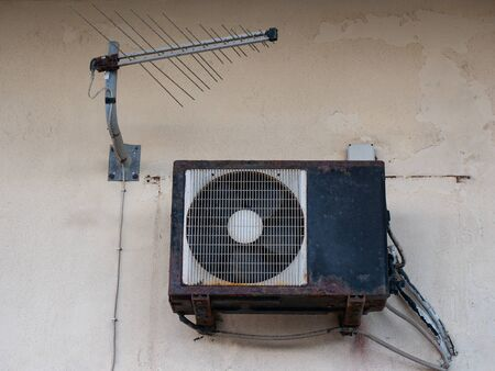 old air conditioner and tv antenna , rusty outdoor unit on a wall