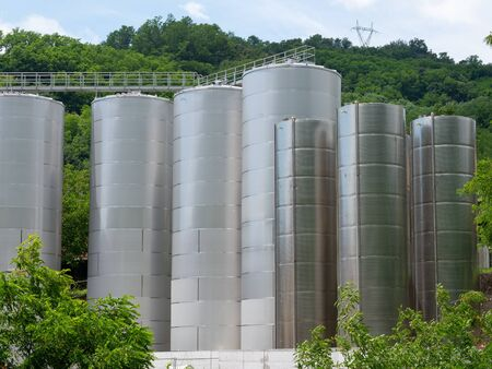 group of large brand new tanks made of stainless steel sheet surrounded by trees